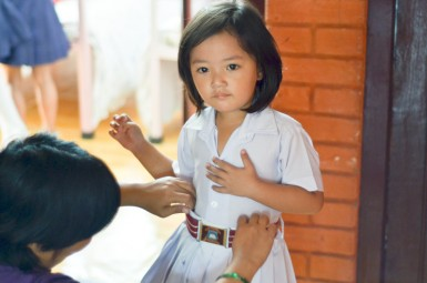 Mom Gyanu helps the littlest kids get ready in school uniforms