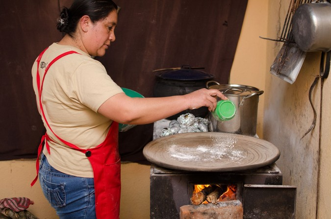 The tortillas are cooked on a wide steel dish above a wood-burning fire. Here, Enma is sprinkling the surface with a bit more lime.