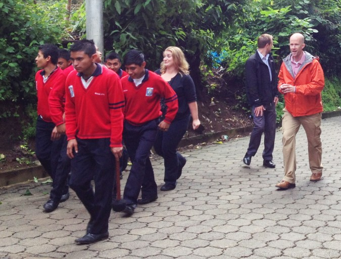 Craig (right), walking with Saber y Gracia students to one of the school's Independence Day marching band parades