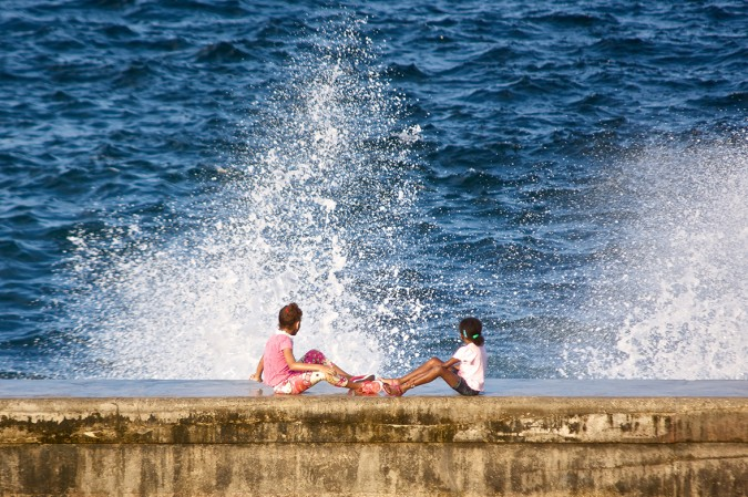 Two girls surprised by a huge wave while resting on the Malecon