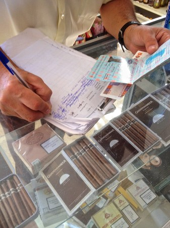 A grocery store clerk writes down passport information for a routine purchase at his store.