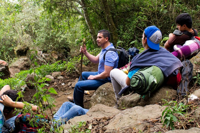 Rudi (center), shares about his faith on Volcán de Agua while Saber y Gracia students listen intently