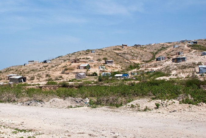 On the way to visit the mass grave for Haiti's earthquake, there was little evidence of its existence. The only buildings nearby were a scattering of homes on the opposite hill.