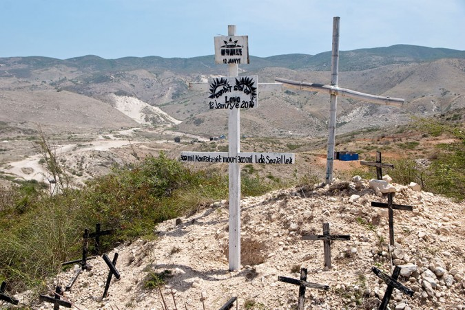 An unkempt dirt path winds up the hill and over the unmarked resting places of thousands. Near the top remains a small cluster of Vodou and Christian crosses.