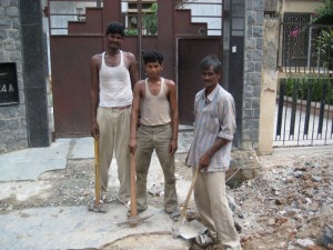 These three guys were hired to demolish this driveway.  They're holding all the tools they'll get to finish the job.