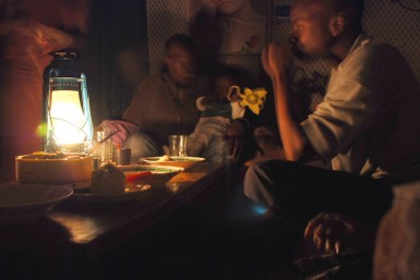 Eating dinner by the light of a lantern.  A common occurance in Kibera.