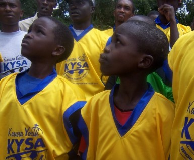 Kids waiting for instructions before trying out their new uniforms on the field.