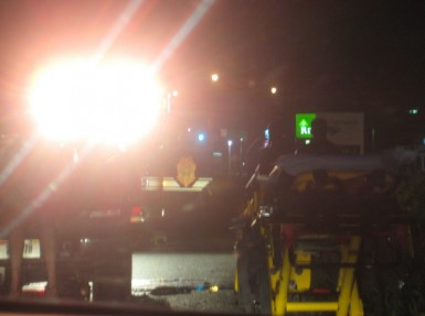 EMTs set up a stretcher as the fire truck's lights illuminated the scene.