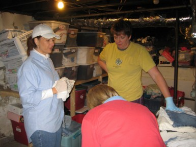 Karen King, Melinda Cecil, and Mary Kay Krambeer sort and inventory clothing donations in order to wrap God's love around homeless young people.